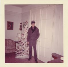 A tall skinny dude next to a tall skinny Christmas tree. No notations.