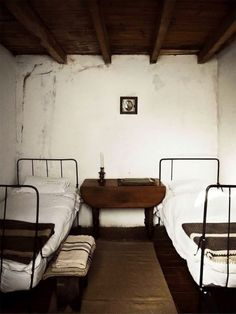lime washed walls + beams + iron beds + linen