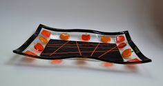 """Halloween fun pumpkins wavy glass fused plate by YafitGlass. Pumpkins are such fun Halloween symbols!!! This plate has small pumpkins in both transparent and opalescent orange color. The center of the plate is black with orange stringers. Black frame and Halloween colors make this plate festive and big enough to hold your Halloween candies. Food safe, hand washing is recommended 12""""x8.5""""."""