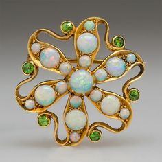 Victorian Opal & Garnet Brooch Pin Pendant 18K Gold. This gorgeous Victorian brooch pin pendant was crafted circa 1880. The 18k yellow gold floral motif brooch is set with crystal opals that show great fire and accented with green demantoid garnets. The brooch is light and delicate with beautiful openwork.