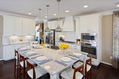 The Hartwood by Miller & Smith at Embrey Mill - White Kitchen with hardwood flooring, large granite island, white cabinets
