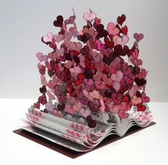 """Book Of Love byDavid Kracov    Inspired by David's love and passion for reading and poetry, the pages of """"Book Of Love"""" transform from the prose of the likes of Browning, Frost, Shelley, and Byron, into a colorful burst of hearts.""""Book Of Love"""" is a hand-made, one-of-a-kind, steel sculpture, and David writes different prose and poems in every sculpture, so each and every """"Book Of Love"""" is truly unique."""