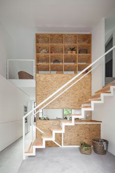 12 Inspiring Examples Of Staircases With Bookshelves | A wooden wall transforms into an open bookshelf as you climb these stairs.