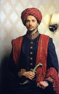 Traditional Pakistani groom apparel worn by a Pakistani model. The shirt is called a sherwani which is a long garment with embroidery on the cuffs. The turban is called by different names - sehri, pagri, kulla depending on the shape and style - and is worn in a tradition called sehri bandi which takes place at the groom's house.
