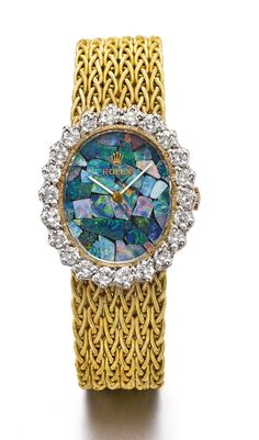 Rolex | • 1400 manual winding movement, 19 jewels • dial set with a mosaic of fire opals • 14k yellow gold oval case, bezel set with diamonds, solid snap on case back • case, dial, movement, and bracelet signed • with 14k yellow gold integrated braided Rolex bracelet