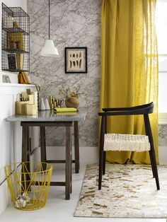 Marble-effect wallpaper creates a striking focal point. Yellow linen curtains cast a rich, golden glow and dark wood furniture adds depth and drama to this home office.
