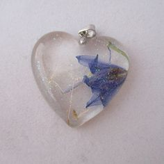 A lovely heart shaped crystal resin pendent with some iridescent glitter, a real dried bluebell and real dandelion wishes. #htlmp #britcraft #hmuk #craftbuzz #gotshop #gotshophr #readytoship #handmade #jewellery #necklace #resin #bluebells #realflowers #flowers #wish #dandelion #heart #love #glitter #sparkle
