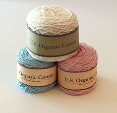 sport weight organic cotton yarnin natural cream, classic baby blue and pink, dyed with alow impact dye process.Grown, spun,dyedin the USA. Sustainable!