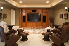 This smaller media room has four recliners with ottomans arranged in a semi-circle around the television, which is inside a built-in wooden cabinet, along with speakers.