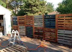 Double high pallet fence with fence posts - but would have this side for exterior (planters on interior) and all stained same colour