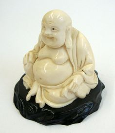 Japanese Antique Ivory Buddah on Wooden Base This charming Netsuke figurine was hand-carved of antique ivory and evinces exquisite craftsmanship. This joyful, carved smiling Buddah is mounted a jet-black wooden base, also ornately handmade. Created in Japan, Netsuke (Japanese: 根付) are miniature sculptures that were originally hand-crafted during the17th-century, during the Edo period. Initially, these [...], $550