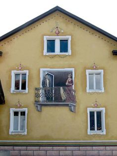 This photo shows a unique balcony facade illusion. A man and a woman appear to be standing outside on the balcony when in fact they are just drawn onto the wall of the building. There are also a number of vases that appear to be sitting on the window frames but they, too, are just drawn illusions