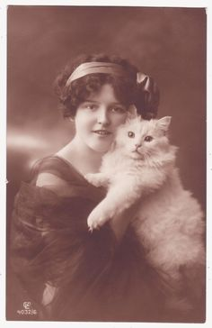"""I love photos like this. The person looks clearly """"olde-tyme"""" but cats' appearance never changes -- so to me it's as if the cat has time-traveled to show up in the photo. :-)"""