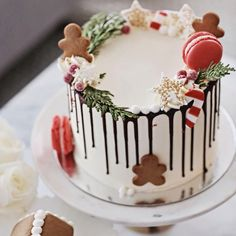 White Christmas cake with macarons, gingerbread men, and candy canes.
