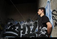 A teenage boy leaning against a graffiti covered wall. © Gina Kelly / Alamy