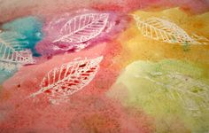 Brilliant! Leaf rubbing with white crayon, then use water colors...