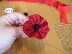 Here's a quick tutorial on how to make a fabric poppy pin for Veterans Day.You will need: needle and thread black buttons or beads (I used a velvety bead from Michaels) scraps of red fabric Material Flowers, Fabric Flowers, Red Fabric, Felt Flowers, Diy Flowers, Veterans Day Coloring Page, Knitted Poppies, Memorial Day Decorations, Poppy Craft