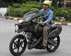 """A worker drives a motorcycle made from recycled materials of spare parts from cars and bicycles at a workshop owned by Roongrojna Sangwongprisarn in Bangkok July 27, 2011. Roongrojna, 54, creates his artworks from recycled spare parts from used cars, motorcycles as well as bicycles. With four shops in Bangkok named """"Ko Art Shop"""", Roongrojna also exports his artworks to clients all over the world. (Photo by Sukree Sukplang/Reuters)"""