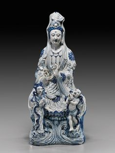 """Chinese Blue & White Porcelain Guanyin  Tall and very heavy, Chinese blue and white porcelain Guanyin; seated atop a lotus pedestal above waves and wearing long robes and veil with Buddhist floral motifs; her hands in mudra and with two attendants standing in front 6-character mark to verso; H: 24"""""""