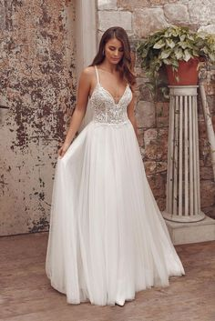 Wow your guests in this A-line gown. The illusion bodice features gorgeous hand beaded embroidered lace and thin beaded straps that crisscross in the back. With a soft English net skirt that makes movement easy. For a more modest look, a version with the bodice lined to the back is also available.