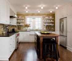 This transitional U-shaped kitchen layout showcases simply white cabinets against a textured brown wall accent.