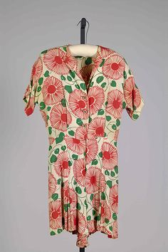 This is a playsuit. It is made of silk with a red and green floral print. It is dated 1940.