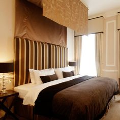 How to create at hotel style bedroom at home. 1)bed is focal point 2)night stands & lamps on either side of bed to create symmetry 3)dramatic headboard or wallpaper behind bed 4)install dimmers