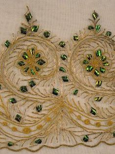 textiles & clothing, , Gold and beetle wing-embroidered lace, 19th century. Three pieces uncut, plus cutout shaped dress parts and flounces on white cotton net, all hand embroidered with couched gold cord studded with green iridescent beetle wings; three flounces.