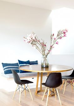 Sweet & simple: round dining table with mid century chairs & banquet adorned with indigo cushions
