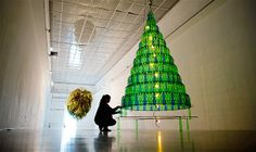 Image: A woman sets up a Christmas tree made of plastic bottles at the Kunstverein in Hanover, Germany, on Nov. 27 (© Julian Stratenschulte/...