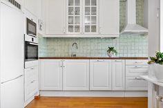 White kitchen with turquoise tiles.