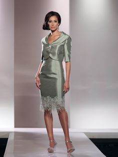 Two-piece shantung and lace suit, sleeveless knee-length sheath with front and back scoop necklines and scalloped lace hemline, matching cropped jacket with elbow-length sleeves and pleated portrait collar accented with jeweled button, suitable for a formal event or as a mother of the bride dress. Sizes: 4 – 20