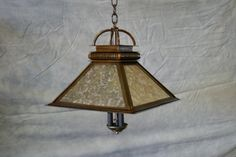 """This is a mission style fixture can be made in many different sizes. This light is pictured in a 16"""" x16"""". Even as the smallest size light it gives off a more light then imagined. This light is shown with gold mica but is also available in many other shades. All finishes are available. Call today and make your custom order."""