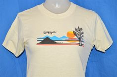 Chest 14.5 in.  Length 22.5 in.  Content: 100% Cotton  Tag Brand: Unbranded  This off-whitetee has a Las Vegas desert scene of a Sunset and its mirage.  This shirt is an Adult Extra Small.      15-04-65836
