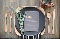 Los Angeles copper and black wedding shoot gold wire decor with white candles and green flower centerpiece decor on brown wood table with copper place setting and silverware with black menu and napkin on top