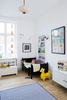 Slide 1 - In this modern style room,the walls and furniture have been painted white to complement each other.The bed and photo frames are black which adds a depth to the calm and cool ambiance of the room.There are small patches of colors used in the forms of accessories and toys as the kid likes cartoon characters.Cool colors on a neutral background with decoration is minimal tones down the mood.The room looks well-furnished and is not cluttered.I like the balance of colors in this room.