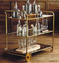 The glamorous Roost Florin Brass Bar Cart harkens back to the Art Deco Era. While amply sized for storage and serving, this golden cart's curving brass lines and three mirrored shelves beckon swanky g Brass Bar Cart, Gold Bar Cart, Bar Antique, Chariot A Roulette, Interiores Art Deco, Bar Trolley, Bar Carts, Drinks Trolley, Kitchen Trolley