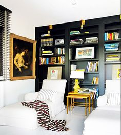 Black built-in library with two lounge chairs and blankets