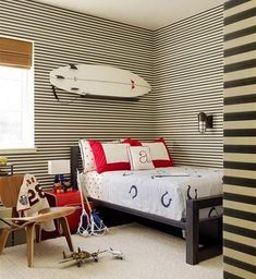 nautical kids room decor with white surfboard above the bed