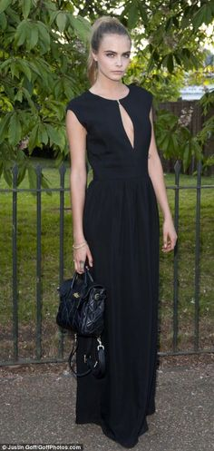 Model behaviour: Cara Delevingne wore a sweeping black gown at the annual event...