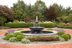 An aluminum & lead fountain in circular driveway in front of house - great choice for a fountain that does not have to covered during winter.