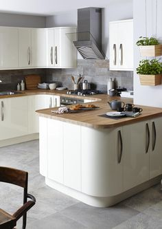 With internal and external curves, soft cream and wooden worktops, this kitchen will add light and space to your home whilst remaining stylish and sophisticated.