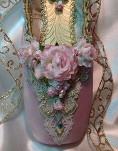 This luxuriously elegant pink and gold decorative pointe shoe the embodies the loveliness of ballet. The beautiful paper roses and rosebuds have