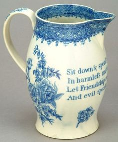 """Late-18th century pearlware jug, probably Swansea, barrel shape with out-turned foot and simple strap handle, printed in blue. Large floral sprays on either side of a verse """"Sit down & spend a Social hour / In harmless mirth & fun / Let Friendship reign be just & Kind / And evil speak of none"""", all beneath a geometric border and with a different geometric border around the inside of the rim."""