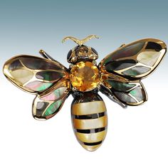 Fancy Honey Bee.  The summertime miracle from this airborne pollinator who flits delightfully from flower to flower is the rich heavenly honey colored citrine on her back.  Hand cut black Tahitian pearl shells adorn her wings with their rich overtones in pink and peacock.  Her tail is golden pearl color.