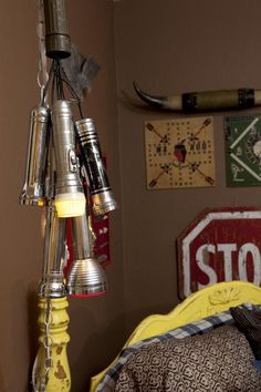 Flashlights serve as a bedside light fixture in this Boy Scout inspired bedroom. See the full transformation here >> http://www.hgtv.com/shows/junk-gypsies/episodes/boyscout-bedroom