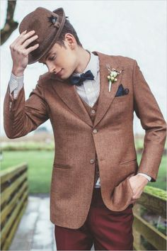 Striped shirt, blue bow tie, regal hat and burgundy trousers make for a super stylish groom
