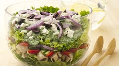 A new twist on popular Greek salad: layered ingredients topped with a spinach and yogurt dressing--rich in veggie goodness!