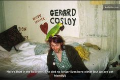 A picture taken of Kurt Cobain in the early sitting on the end of the double bed he shared with Courtney Love. And with a parrot resting on his head, of course. The graffiti, however, has long since disappeared Kurt Cobain Photos, Nirvana Kurt Cobain, Nirvana Band, Anthony Kiedis, John Waters, Courtney Love, Robert Smith, Nicolas Cage, Al Pacino