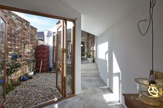 Amazing glass walls/doors open completely in the Dolls House,© Frasen Marsden-doors open from kitchen and bedroom onto tiny courtyard garden with pebbled surface. great tall narrow rain barrel in rust-red color, vertical garden of wire along brick facade